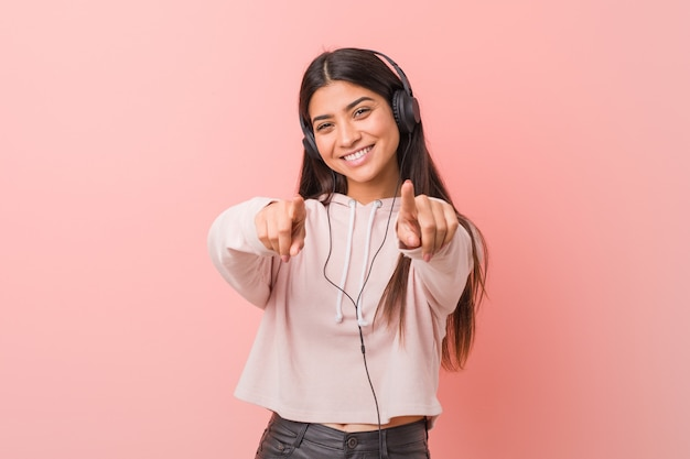 Young arab woman listening to music cheerful smiles pointing to front.