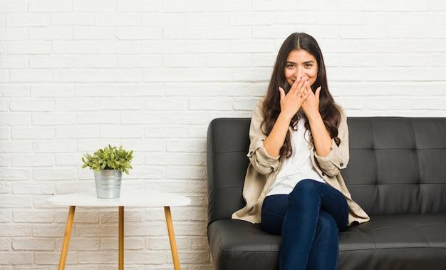 何かについて笑って、手で口を覆っているソファに座っている若いアラブ女性。
