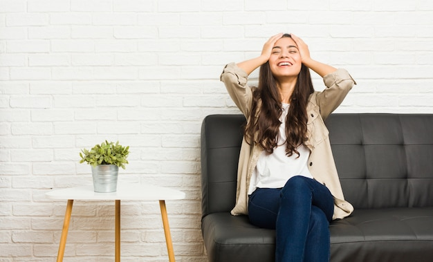 ソファに座っている若いアラブ女性は、手を頭の上に置いて喜んで笑います。幸福の概念。
