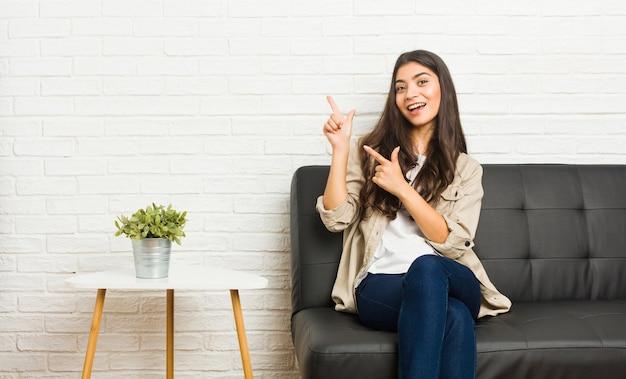 ソファに座ってコピースペースを指差し、興奮と欲望を表現する若いアラブの女性。