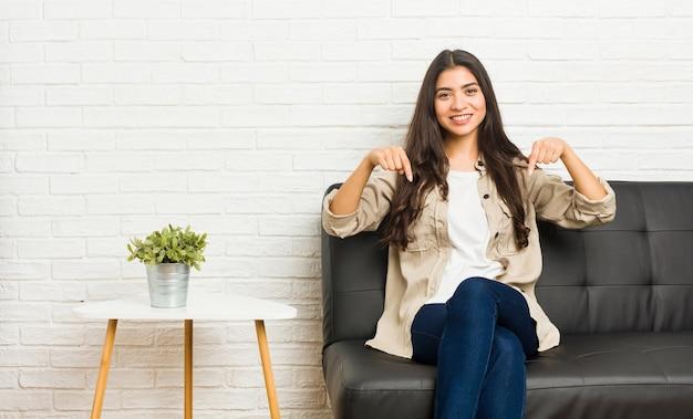 ソファに座っている若いアラブの女性は、指で下向き、前向きな気持ちです。