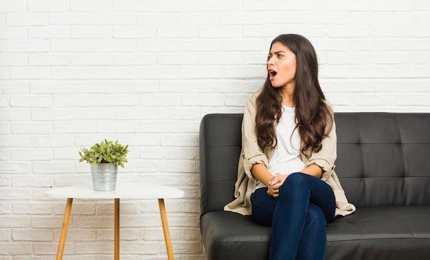 コピースペースに向かって叫んでソファに座っている若いアラブの女性