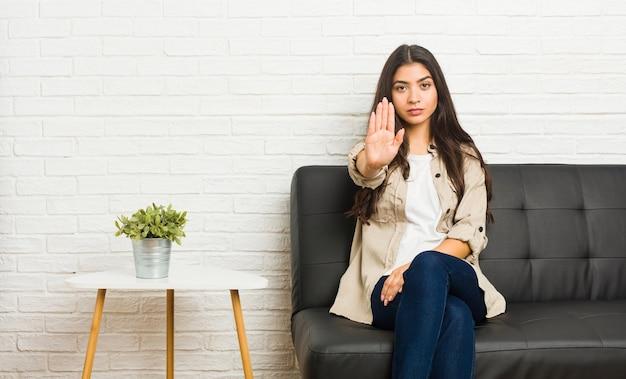 ソファに座って、手を伸ばして一時停止の標識を示し、あなたを妨げている若いアラブの女性。
