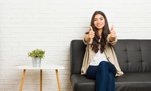 親指でソファに座っている若いアラブ女性ups、何かについての歓声、サポートと尊重の概念。
