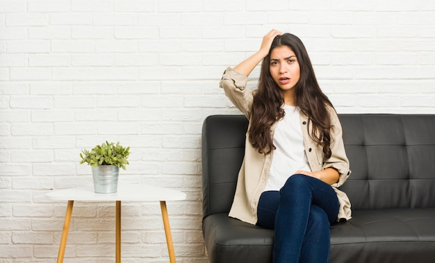 Young arab woman sitting on the sofa being shocked, she has remembered important meeting.