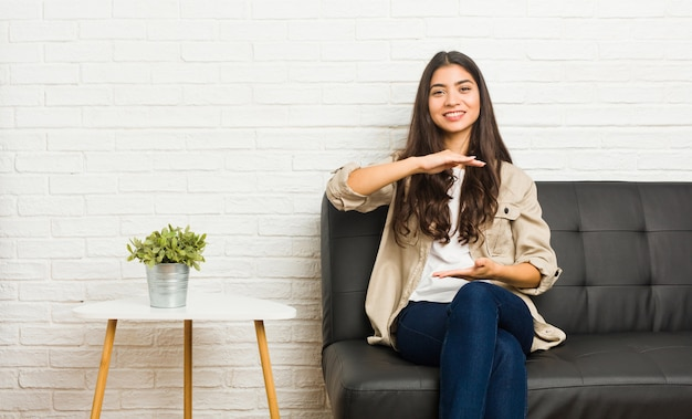 Young arab woman sitting on the sofa holding something with both hands, product presentation.