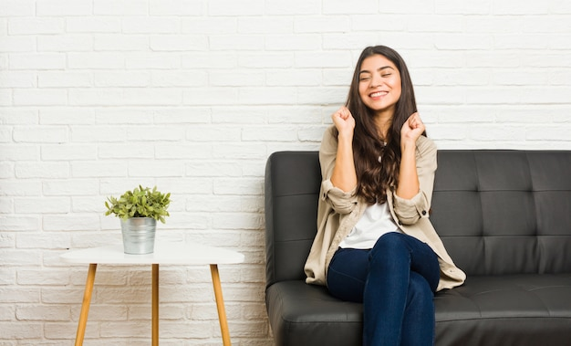Young arab woman sitting on the sofa raising fist, feeling happy and successful. victory concept.