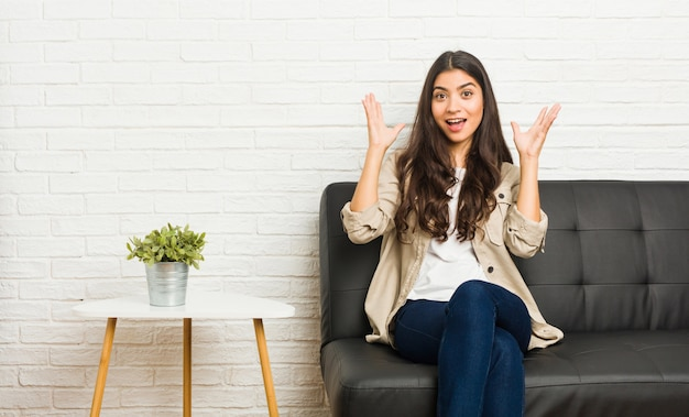 Young arab woman sitting sofa receiving a pleasant surprise, excited and raising hands.