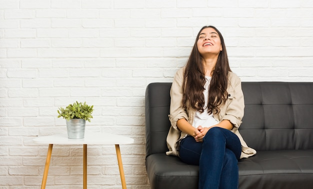 Young arab woman sitting on the sofa relaxed and happy laughing, neck stretched showing teeth.