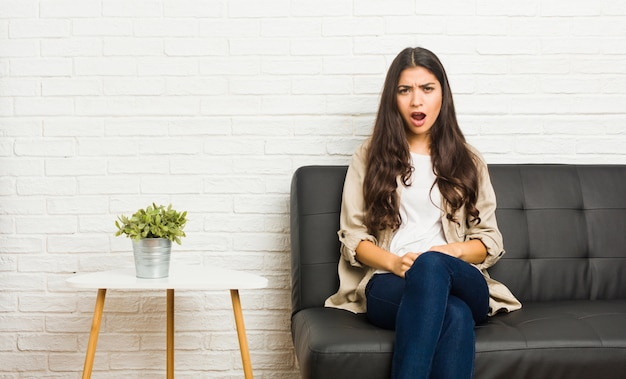 Young arab woman sitting on the sofa screaming very angry and aggressive.