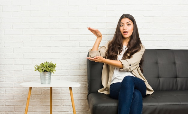 Young arab woman sitting on the sofa shocked