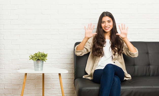 Young arab woman sitting on the sofa showing number ten with hands.