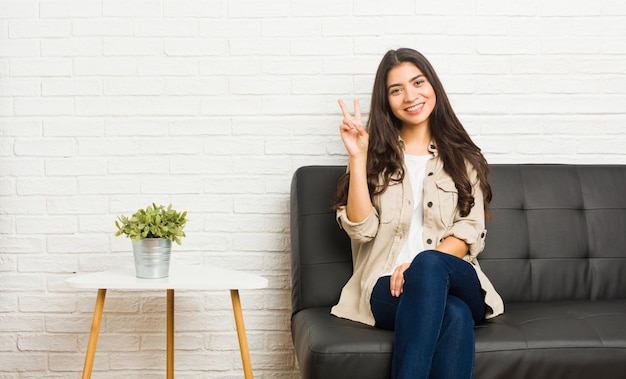 Young arab woman sitting on the sofa showing victory sign and smiling broadly.
