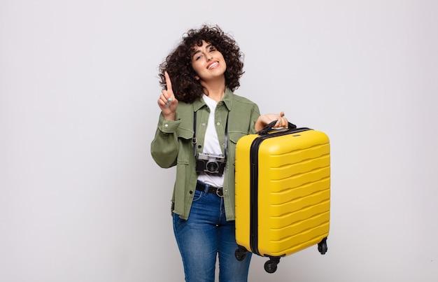 笑顔でフレンドリーに見える若いアラブの女性、手前でナンバーワンまたは最初を示し、旅行の概念をカウントダウン