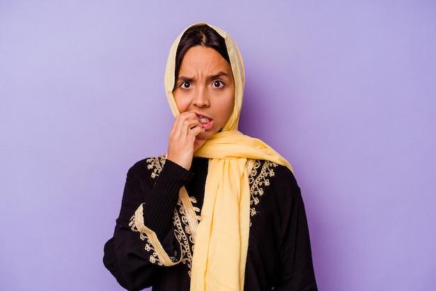 손톱, 긴장 하 고 매우 불안을 물고 보라색 배경에 고립 된 전형적인 아라비아 의상을 입고 젊은 아랍 여자.
