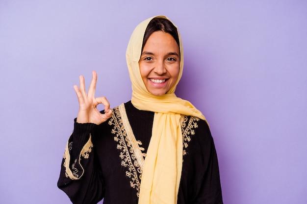 보라색 배경 명랑 하 고 확신 보여주는 확인 제스처에 고립 된 전형적인 아라비아 의상을 입고 젊은 아랍 여자.