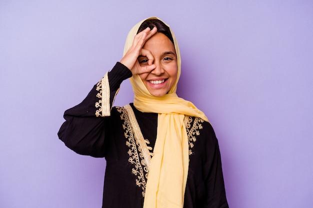 보라색 배경에 고립 된 전형적인 아라비아 의상을 입고 젊은 아랍 여자는 눈에 확인 제스처를 유지 흥분.
