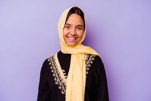 행복 하 고 웃 고 쾌활 한 보라색 배경에 고립 된 전형적인 아라비아 의상을 입고 젊은 아랍 여자.