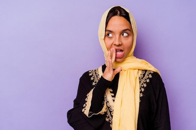 보라색 배경에 고립 된 전형적인 아라비아 의상을 입고 젊은 아랍 여성은 비밀 뜨거운 제동 뉴스를 말하고 옆으로보고있다