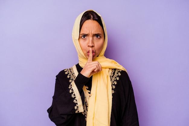 비밀을 유지하거나 침묵을 요구하는 보라색 배경에 고립 된 전형적인 아라비아 의상을 입고 젊은 아랍 여성.