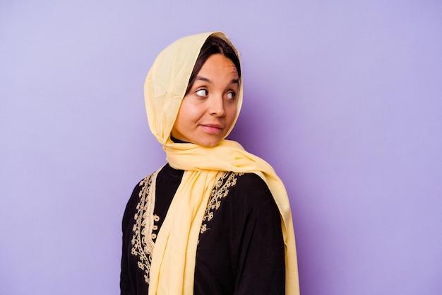 보라색 배경에 고립 된 전형적인 아라비아 의상을 입고 젊은 아랍 여성은 옆으로 웃고, 밝고 쾌적합니다.