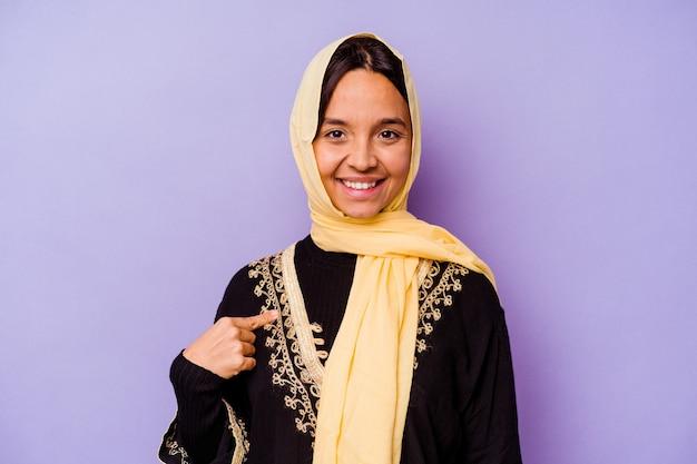 자랑스럽고 자신감, 셔츠 복사 공간을 손으로 가리키는 보라색 배경 사람에 고립 된 전형적인 아라비아 의상을 입고 젊은 아랍 여성