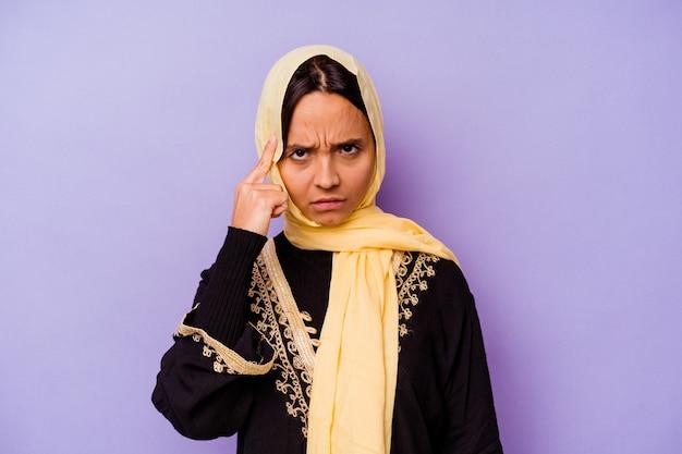 손가락으로 사원을 가리키는 보라색 배경에 고립 된 전형적인 아라비아 의상을 입고 젊은 아랍 여자 생각, 작업에 초점을 맞춘.
