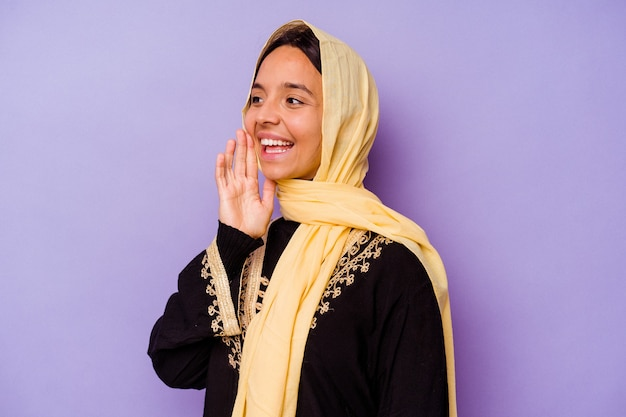 보라색 배경 소리와 열린 된 입 근처에 손바닥을 들고에 고립 된 전형적인 아라비아 의상을 입고 젊은 아랍 여자.
