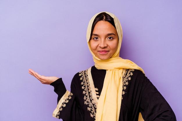 손바닥에 복사 공간을 표시 하 고 허리에 다른 손을 잡고 보라색 배경에 고립 된 전형적인 아라비아 의상을 입고 젊은 아랍 여자.