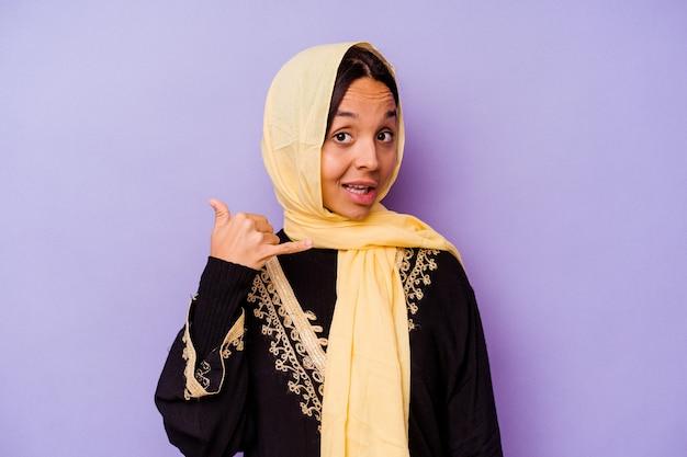 손가락으로 휴대 전화 제스처를 보여주는 보라색 배경에 고립 된 전형적인 아라비아 의상을 입고 젊은 아랍 여자.