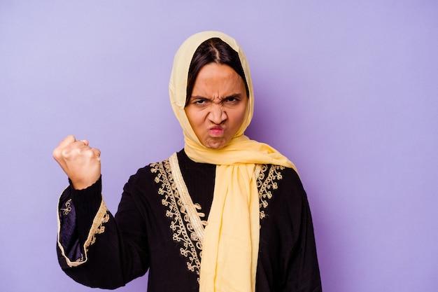 카메라, 공격적인 표정에 주먹을 보여주는 보라색 배경에 고립 된 전형적인 아라비아 의상을 입고 젊은 아랍 여자.