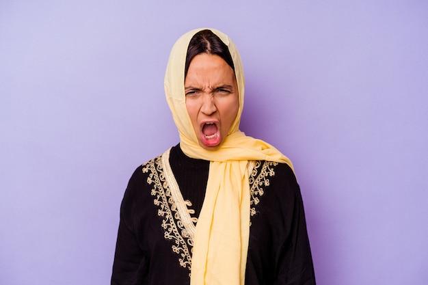Молодая арабская женщина в типичном арабском костюме, изолированном на фиолетовой стене, кричала очень сердито и агрессивно.