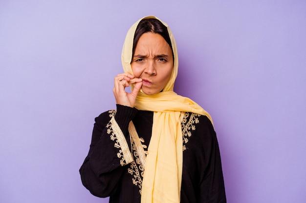 Молодая арабская женщина в типичном арабском костюме, изолированном на фиолетовой стене с пальцами на губах, хранит секрет.