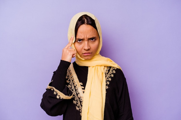 Young arab woman wearing a typical arabian costume isolated on purple background pointing temple with finger, thinking, focused on a task.