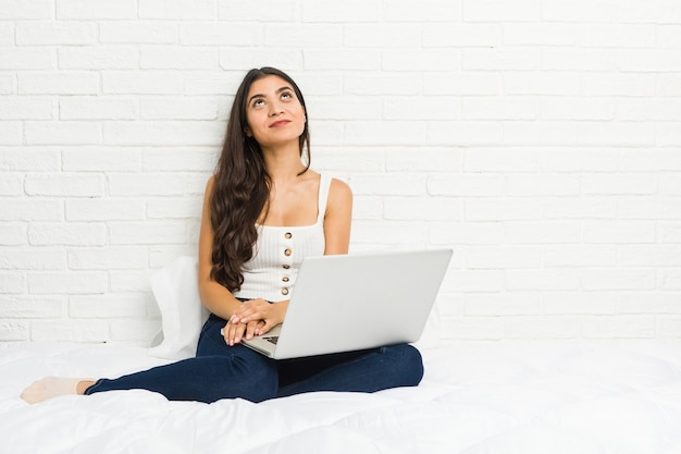 Young arab woman working with her laptop on the bed dreaming of achieving goals and purposes