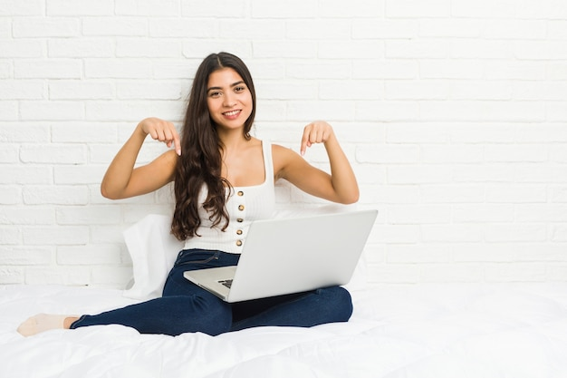 Young arab woman working with her laptop on the bed points down with fingers, positive feeling.
