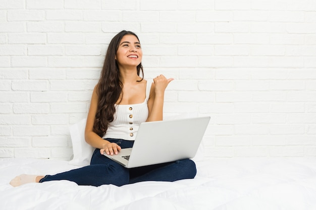 Young arab woman working with her laptop on the bed points with thumb finger away, laughing and carefree.