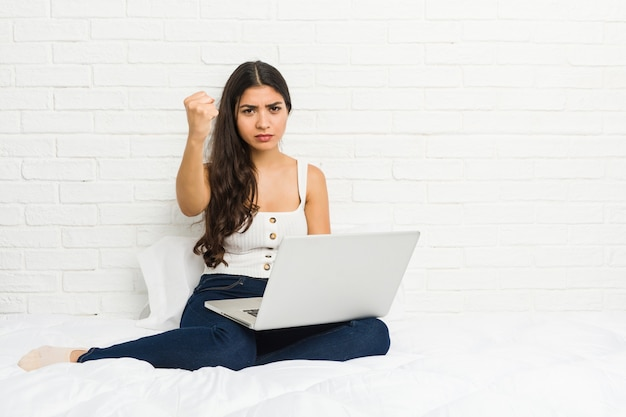 Young arab woman working with her laptop on the bed showing fist to camera, aggressive facial expression.