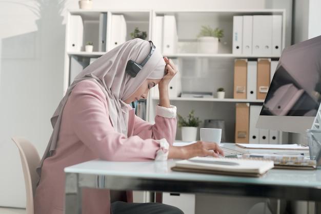 Молодая арабская бизнес-леди в хиджабе устала от работы в колл-центре, сидя за столом и склонив голову на руку