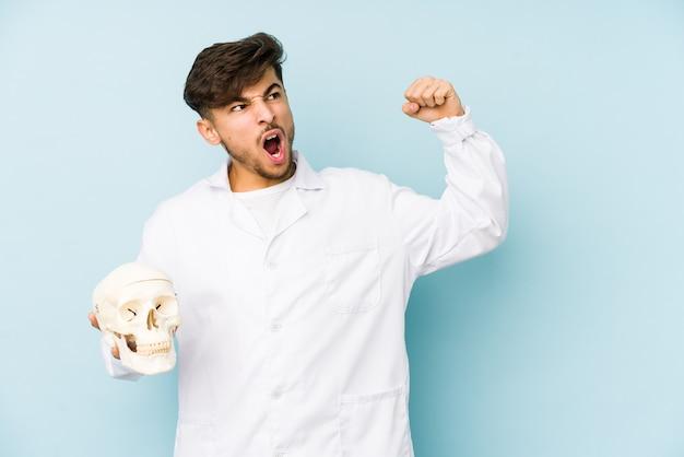 Молодой арабский доктор человек держит кулак повышения черепа после победы, концепции победителя.