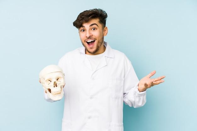 Молодой арабский доктор мужчина держит череп, получая приятный сюрприз, возбужденный и поднимающий руки.