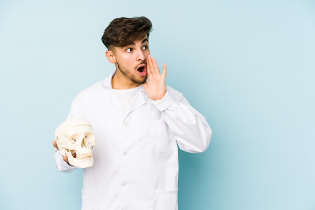 Young arabian doctor man holding a skull is saying a secret hot braking news and looking aside