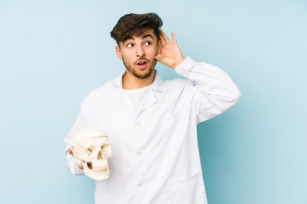 Young arabian doctor man holding a skull trying to listening a gossip.