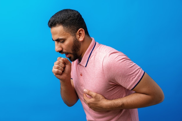 Young arabian man feeling ill and coughing against blue background