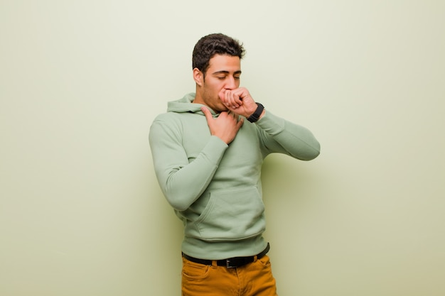Young arabian man feeling ill with a sore throat and flu symptoms, coughing with mouth covered against flat wall