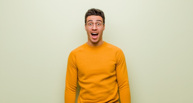 Young arabian man feeling terrified and shocked, with mouth wide open in surprise against flat wall