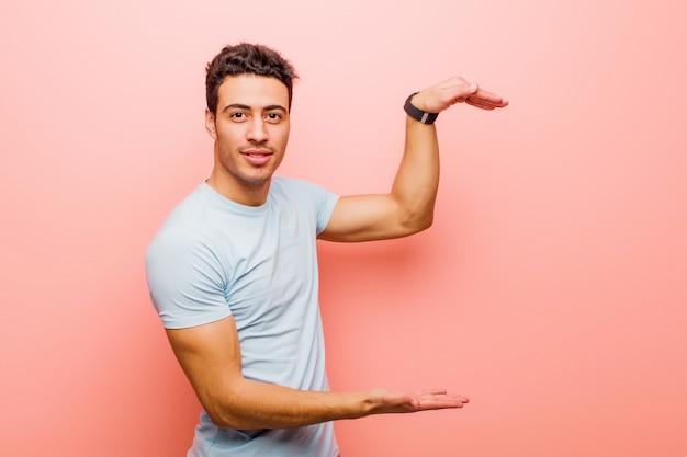 Молодой арабский мужчина держит объект обеими руками на боковой копией пространства, показывая, предлагая или рекламируя объект против розовой стены