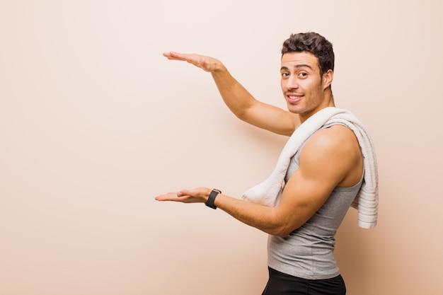 Молодой аравийский человек держа объект обеими руками на бортовом космосе экземпляра, показывая, предлагая или рекламируя объект. спортивная концепция