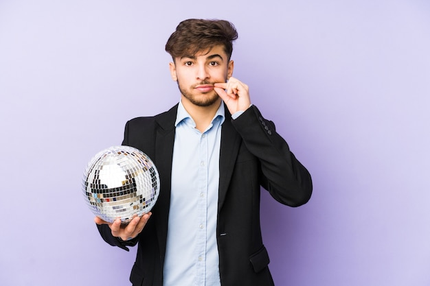 Young arabian man holding a party ball isolated with fingers on lips keeping a secret.