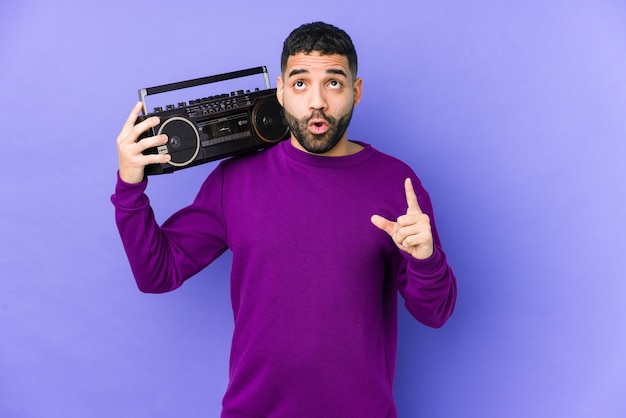 Young arabian man holding a radio cassette isolated young arabian man listening music pointing upside with opened mouth.